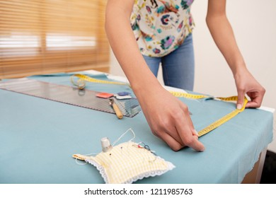 Mid section view of young fashion designer woman measuring pattern on fabric, using tape and sewing tools, home interior. Fashionable faceless female, hand making clothes, creative hobby lifestyle.