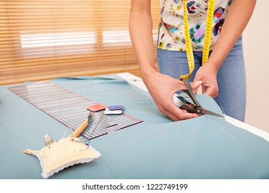 Mid section view of young fashion designer woman cutting pattern on fabric, using scissors and sewing tools, home interior. Faceless female, hand making clothes, creative hobby lifestyle.