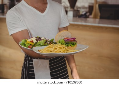 Mid section of waiter holding plate with food while standing by counter in cafe