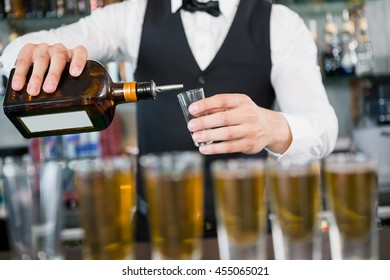 Mid section of waiter making shots at bar counter in restaurant