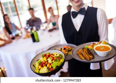Mid section of waitress holding food on plate in restaurant