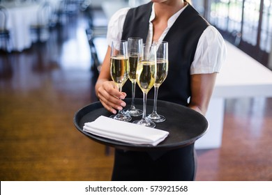 Mid section of waitress holding serving tray with champagne flutes in restaurant