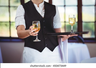 Mid section of waitress offering a glass of wine in restaurant