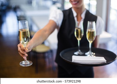 Mid section of waitress offering a glass of champagne in restaurant