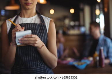 Mid section of waitress taking order at restaurant
