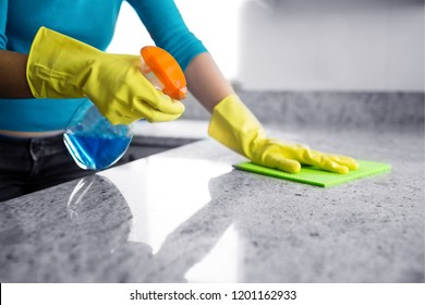 Mid section of woman cleaning kitchen counter at home