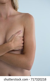 Mid section of woman covering breast while standing against gray background