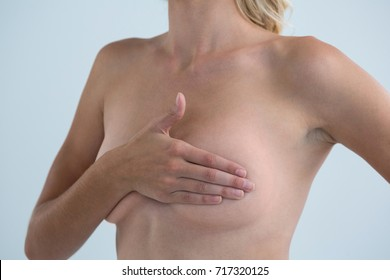 Mid section of woman with hand on breast standing against gray background