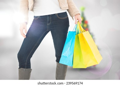 Mid section of woman holding shopping bags against blurry christmas tree in room