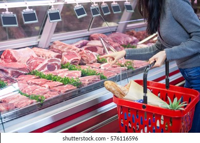 Mid section of woman pointing at meat in display at supermarket