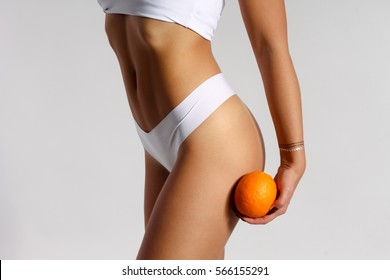 Mid section of woman with sport body holding orange near her leg, anti-cellulite concept