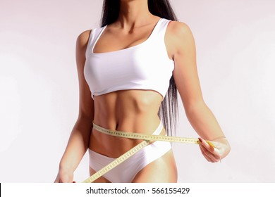 Mid section of woman with sport body measuring her waist with measuring tape