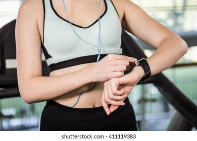 Mid section of woman using smartwatch at the gym