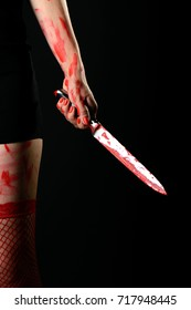 Mid section of woman wearing red stockings holding bloody knife