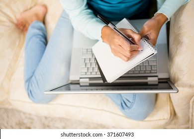 Mid section of woman writing on notepad with laptop on her legs while sitting on the sofa
