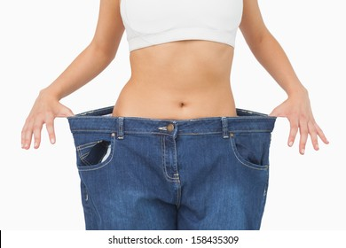 Mid section of young slim woman wearing too big jeans on white screen