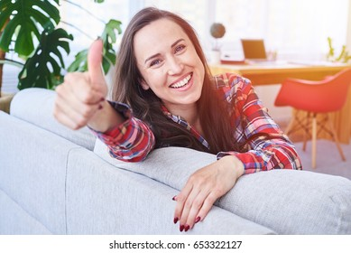 Mid shot of appealing girl having rest and putting thumb up