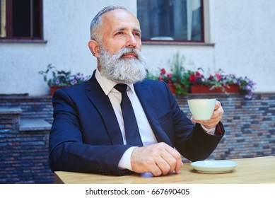 Mid shot of bearded male drinking coffee while sitting