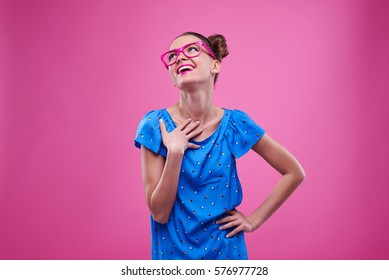 Mid shot of charmed girl with hand on chest looking upwards. Trendy girl in bright outfit with hand on hip looking up