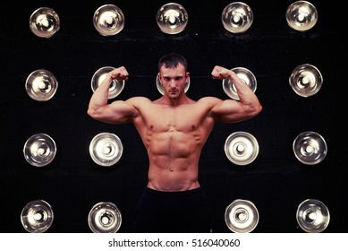 Mid shot of   front double bicep pose of muscular male in studio lights