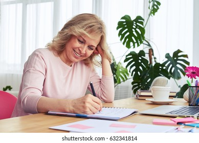 Mid shot of good-looking woman with beautiful smile writing in notebook while sitting at table