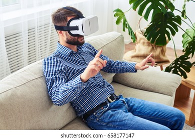 Mid shot of guy in blue shirt working in virtual reality glasses sitting on sofa