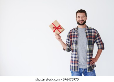 Mid shot of happy bearded man with present box standing isolated over white background