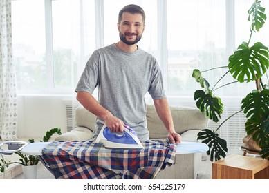 Mid shot of lovely husband ironing attentively shirt on ironing board