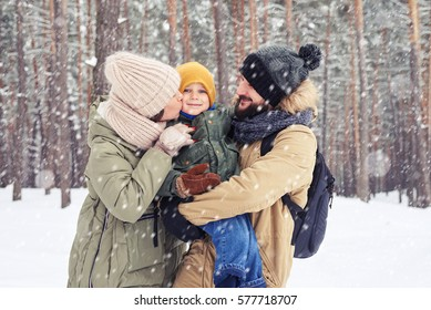 Mid shot of loving family in the forest spending time together. Cheer couple look embrace over a picturesque wintry forest. Wrapped in a warm clothes, looking at the camera