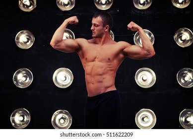 Mid shot of male model who is standing on front double bicep pose. Young bodybuilder motivated look showing his pumped biceps and triceps