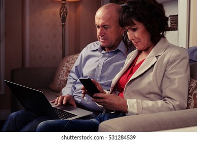 A mid shot of man surfing the web and riant woman regarding her phone. A pair sitting on the brown settee with patterned pillows