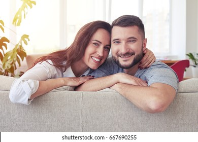 Mid shot of marvelous lady and sir hugging and relaxing on sofa