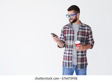 Mid shot of modern bearded man in blue glasses drinking coffee and texting on phone