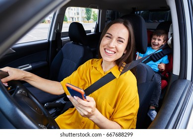 Mid shot of a mother driving a car, buckled the seat belt, holding phone. Laughing boy on back seat