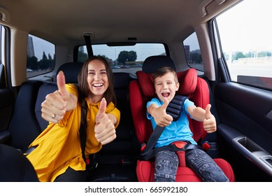 Mid shot of a mother and her child, both buckled the seat belt. Family holding their thumbs up, having fun together