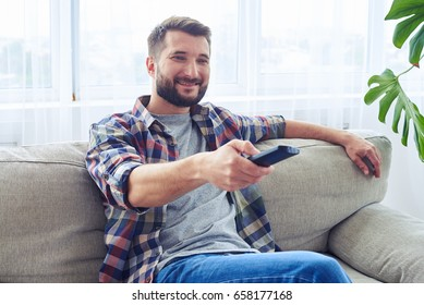 Mid shot of nice guy switching channel with remote control
