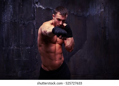 Mid shot of powerful sportsman who is practicing a jab in black boxing gloves over background. His body is firm with strong muscles