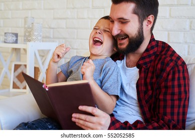 A mid shot of son a dad laughing and reading a book in brown cover. Father wearing red checkered shirt and son wearing grey t-shirt