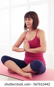 Mid shot of the woman holding hands together, crossed legs. Brunette practicing meditation indoors