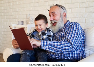 Mid side shot of elated grandfather and his son while reading a story. Smiling grandpa with his grandson enjoy their time