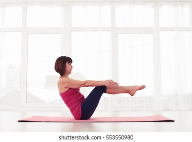 Mid side view shot of woman doing ab crunches with legs raised. Developing a proper strength in upper abdominals muscles