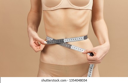 Mid waist portrait of undressed underweight caucasian female model measuring her waist with a tailor meter, looking skinny with protruding ribs and hip bones. Anorexia concept