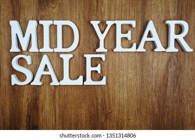 Mid Year Sale alphabet letters on wooden background business concept