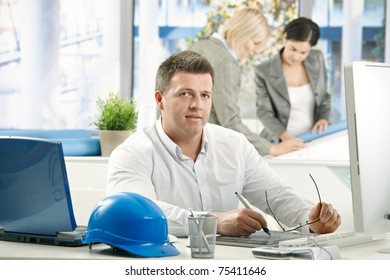 Mid-adult architect working in office, looking at camera, busy coworkers in background.?