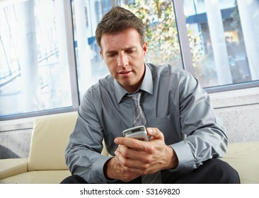 Mid-adult businessman looking down at mobile phone sitting on beige sofa in bright office.
