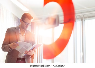 Mid-adult businessman reading file in creative office