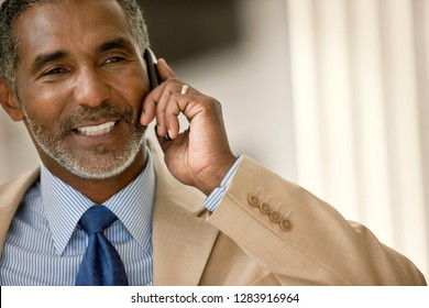 Mid-adult businessman smiling while talking on his cell phone.