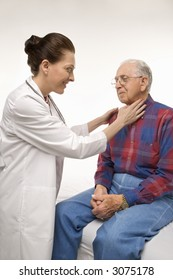 Mid-adult Caucasian female doctor checking an elderly Caucasian male's pulse.