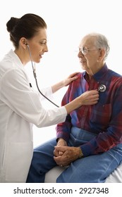 Mid-adult Caucasian female doctor listening  to elderly Caucasian male's heart with stethoscope.