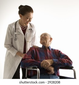 Mid-adult Caucasian female doctor looking at an elderly Caucasian male in wheelchair.